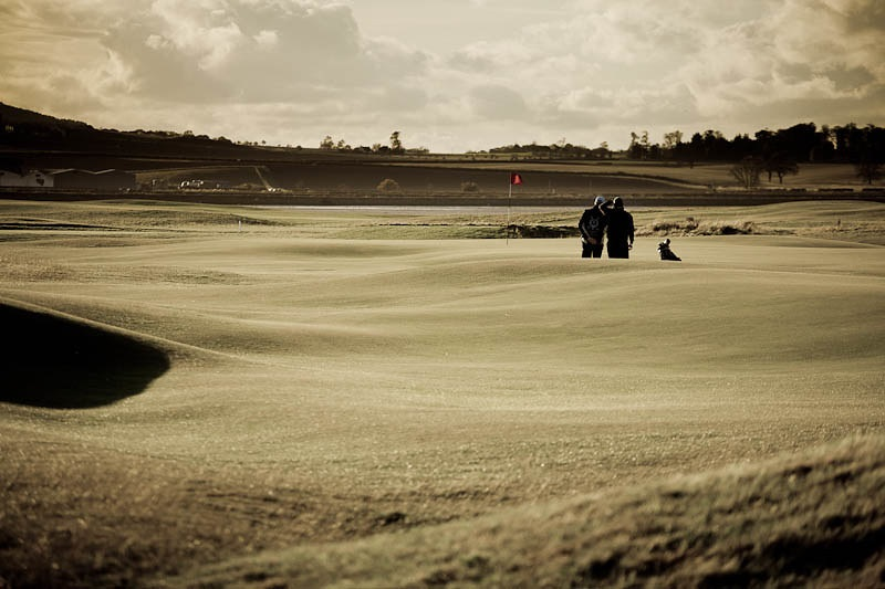 Two golfers line up a putt at St Andrews golf links